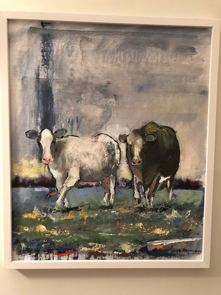 Två kor går på en grön äng. De verkar fridsamma och ser ut att må fint.